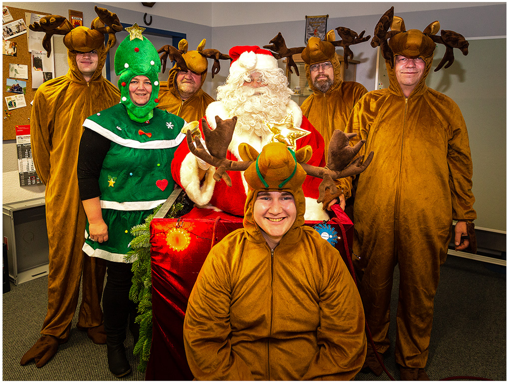 Der Weihnachtsmann mit seinen Rentieren und dem Weihnachtsbaum als Gehilfen